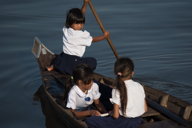 Three girls getting themselves to school at Prek Toal floating village.